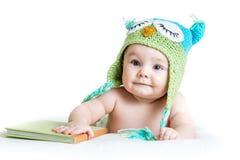 Bebê na coruja feita malha engraçada do chapéu com livro Imagens de Stock