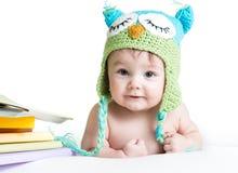 Bebê na coruja feita malha engraçada do chapéu com livros Fotos de Stock