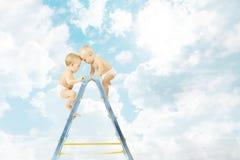 Bebê na escada portátil que luta pelo primeiro lugar sobre o céu azul imagem de stock