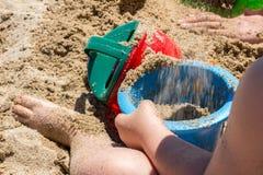 Bebê na praia marrom da areia que joga com cubeta e pá da praia imagem de stock royalty free