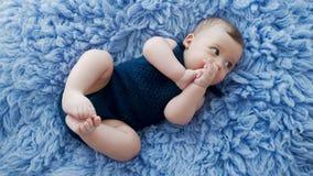 Bebê na roupa feita malha azul de um fato-macaco filme
