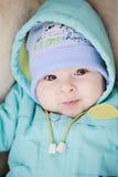 Bebê no casaco azul que sorri na câmera Imagens de Stock Royalty Free