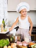 Bebê no chapéu do cozinheiro que cozinha a sopa fotografia de stock