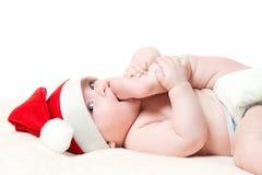 Bebê no chapéu do Natal que joga com seus pés Fotografia de Stock