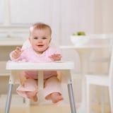 Bebê no highchair que espera para ser alimentado Imagens de Stock Royalty Free