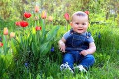 Bebê no jardim com flores Foto de Stock Royalty Free