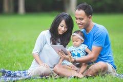 Bebê no parque usando o PC da tabuleta fotografia de stock