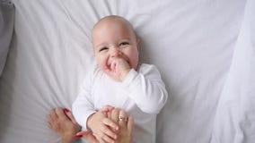 Bebê no t-shirt branco que encontra-se em uma cama branca e que ri olhando o movimento lento de opinião superior da câmera vídeos de arquivo
