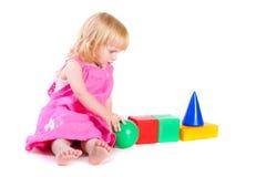 Bebê no vestido cor-de-rosa que joga com blocos brilhantes Fotografia de Stock
