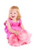 Bebê no vestido cor-de-rosa que joga com urso de peluche Fotografia de Stock