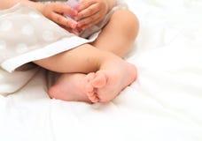 Bebê no vestido que joga seus pés Fotografia de Stock Royalty Free
