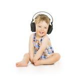 Bebê nos fones de ouvido que escuta a música, criança pequena isolada sobre Fotos de Stock Royalty Free