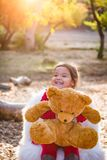 Bebê novo bonito da raça misturada que abraça Teddy Bear Outdoors imagens de stock