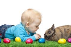 Bebê novo masculino no prado com coelho de Easter fotos de stock royalty free