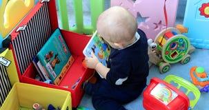 Bebê novo que joga com seus brinquedos no cercadinho filme