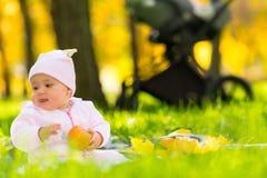 Bebê novo satisfeito fora em um parque do outono fotografia de stock