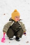 Bebê pensativo com pá (inverno) Fotografia de Stock Royalty Free