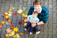 Bebê pequeno adorável e pai novo no parque do outono no dia morno ensolarado de outubro com carvalho e folha de bordo Queda imagem de stock