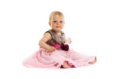 Bebê pequeno adorável no vestido cor-de-rosa que senta-se no assoalho fotografia de stock