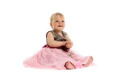 Bebê pequeno adorável no vestido cor-de-rosa que senta-se no assoalho imagem de stock royalty free