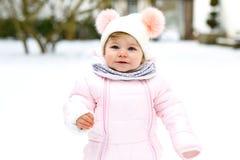 Bebê pequeno adorável que faz primeiras etapas fora no inverno Criança bonito que aprende o passeio Criança que tem o divertiment imagem de stock royalty free