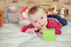 Bebê pequeno bonito de sorriso engraçado da opinião uma do retrato do close up com o cabelo louro que encontra-se na cama com a c Fotos de Stock