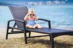 Bebê pequeno bonito no roupa de banho e em óculos de sol cor-de-rosa vestindo Foto de Stock Royalty Free