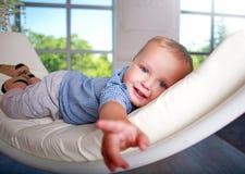 Bebê pequeno bonito no sofá em casa na sala com luz solar foto de stock royalty free