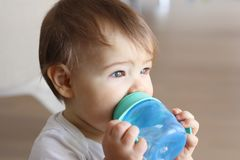 Bebê pequeno bonito que guarda suas garrafa e água potável azuis imagens de stock