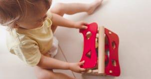 Bebê pequeno bonito que joga com a casa de madeira pequena filme