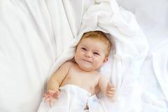 Bebê pequeno bonito que joga com próprios pés após ter tomado o banho Menina bonita adorável envolvida nas toalhas brancas Fotografia de Stock Royalty Free