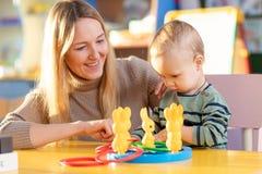 Bebê pequeno bonito que joga com sua mãe com anéis fotografia de stock royalty free