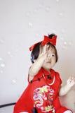 Bebê pequeno chinês engraçado em bolhas de sabão vermelhas do jogo do cheongsam Imagens de Stock Royalty Free