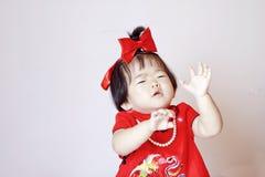 Bebê pequeno chinês no cheongsam vermelho assustado por bolhas de sabão Fotos de Stock Royalty Free
