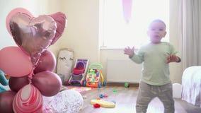 Bebê pequeno com ballons em casa que anda primeiramente etapas em seu aniversário, um ano