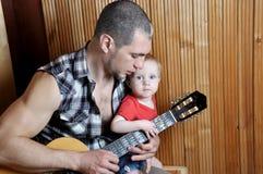 Bebê pequeno com seu pai do moderno que joga a guitarra no fundo de madeira Fotografia de Stock