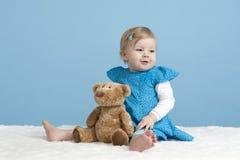 Bebê pequeno com urso de peluche, no azul fotografia de stock royalty free