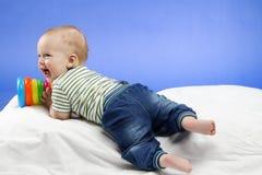 Bebê pequeno de riso, sentando-se na cobertura branca com um brinquedo nas mãos, tiro do estúdio, isolado no fundo azul Imagens de Stock