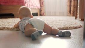 Bebê pequeno de sete meses, rastejando no assoalho na sala de crianças Caçoe o rastejamento no tapete, vista traseira video estoque