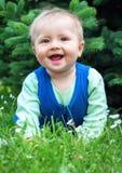 Bebê pequeno de sorriso bonito que encontra-se em uma grama verde fresca em um parque Fotografia de Stock Royalty Free