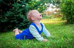 Bebê pequeno de sorriso bonito que encontra-se em uma grama verde fresca em um parque Imagem de Stock Royalty Free