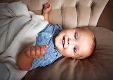 Bebê pequeno do sorriso feliz no sofá em casa na sala foto de stock royalty free