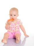 Bebê pequeno doce que come uma cenoura que senta-se no assoalho no branco Imagens de Stock