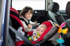 Bebê pequeno e seu irmão mais idoso, viajando nos bancos de carro, g imagens de stock