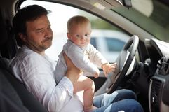 Bebê pequeno e seu pai que têm o divertimento em um carro Fotos de Stock Royalty Free