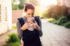 Bebê pequeno e sua mãe que andam fora durante o por do sol A mãe é guardando e agradando seu bebê, babywearing no portador imagens de stock