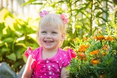 Bebê pequeno feliz bonito em um fundo brilhante verde do verão fotografia de stock royalty free