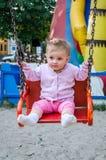 Bebê pequeno feliz com um fecho bonito em sua equitação da cabeça e do revestimento em um balanço chain no parque de diversões Imagens de Stock Royalty Free
