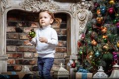Bebê pequeno feliz que decora a árvore de Natal com os brinquedos em feriados Fotografia de Stock