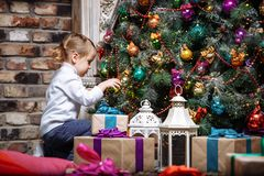Bebê pequeno feliz que decora a árvore de Natal com os brinquedos em feriados Imagem de Stock